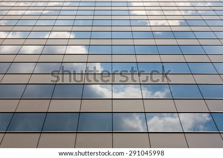 Reflection of blue sky and cloud on the mirror of building  - stock photo