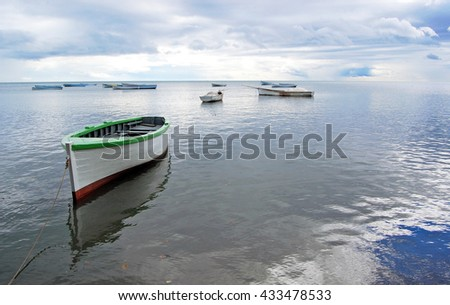 Reflection of boat at low tide on fisher village beach in Mauritius