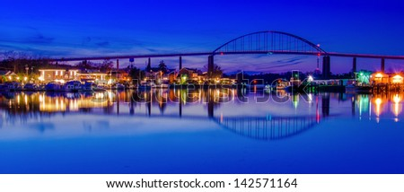 Reflection of Chesapeake City in the Chesapeake and Delaware Canal, Maryland. - stock photo