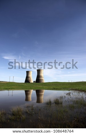 Reflection of closed, idle nuclear power generation cooling towers in country pond. - stock photo