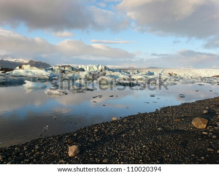 Reflection of clouds and floating icebergs in Jokulsarlon glacier lake in Iceland. - stock photo