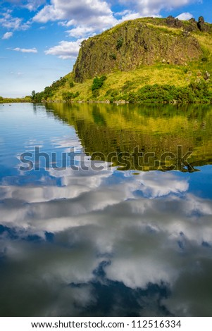Reflection of clouds in a mountain lake in Scotland - stock photo