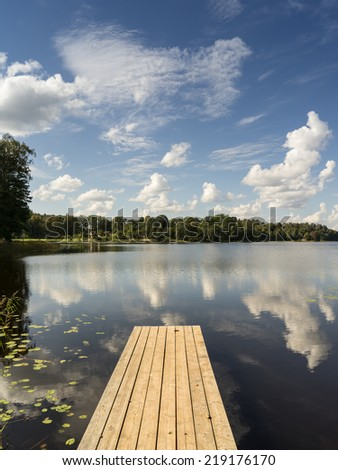 reflection of clouds in the lake with boardwalk and trees in background