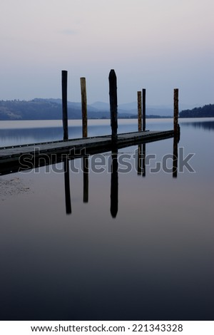 Reflection of dock at sunrise on the calm Chatcolet Lake in north Idaho. - stock photo