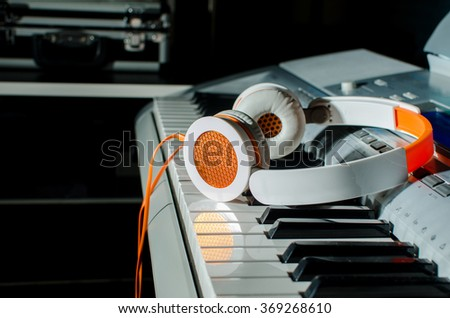 Reflection of earphones on keyboard - stock photo