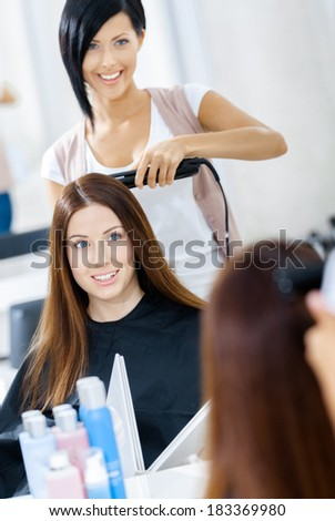 Reflection of hairdresser doing hair style for woman in hairdress salon. Concept of fashion and beauty - stock photo