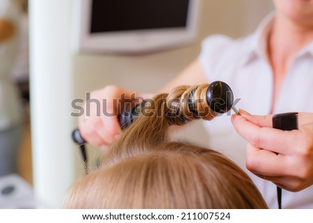 Reflection of hairdresser doing hair style for woman in hairdresser's. Concept of fashion and beauty - stock photo