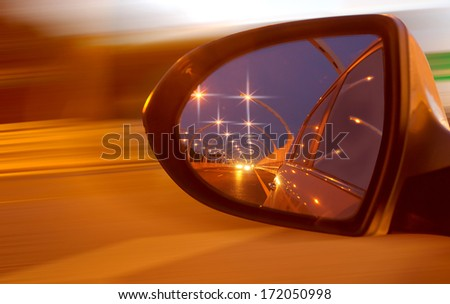 Reflection of high-speed road on car's mirror - stock photo