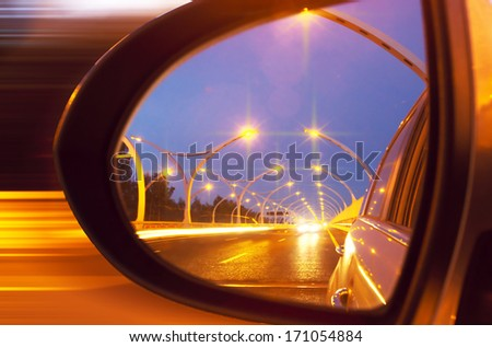 Reflection of high-way on car mirror - stock photo