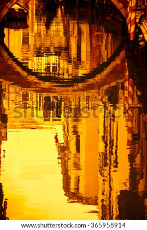 Reflection of houses and small bridge in the water of a narrow canal. Venice (Italy). Selective focus. Golden sunset light. Toned photo. - stock photo