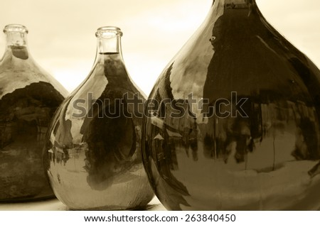 Reflection of medieval street in big dirty bottles with colored liquid. Cityscape in bottle glass. Sepia aged photo. Selective focus on the reflection in right bottle. - stock photo