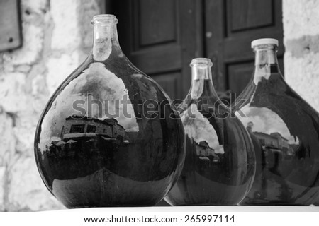 Reflection of medieval town street in big dirty bottles with colored liquid. Cityscape in bottle glass. (Provence France) Black and white aged photo. Selective focus on left bottle.