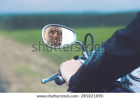 Reflection of Motorcycle Driver in Rearview Mirror - stock photo