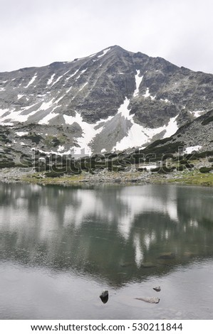 Reflection of mountain Rila in small lake in the National Park Rila, Bulgaria