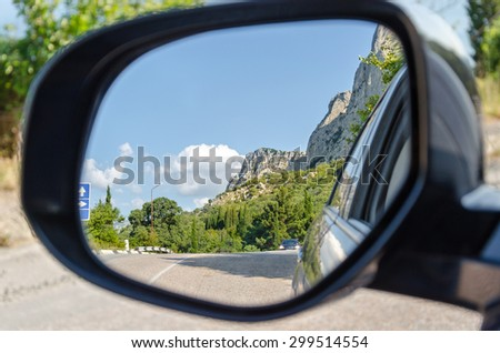 Reflection of mountains and road in a rear-view mirror - stock photo