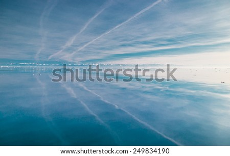 Reflection of mountains in the ice - stock photo