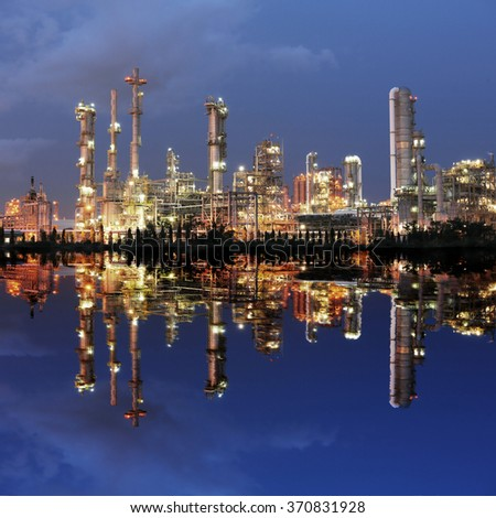 Reflection of petrochemical plant at night - stock photo