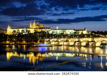 Reflection of Prague caste and the Charles bridge at dusk - stock photo