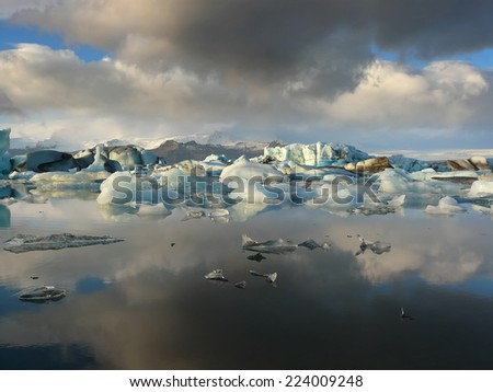 Reflection of rainclouds and floating icebergs in Jokulsarlon glacier lake in Iceland. This is a lake where icebergs calve from Vatnajokull glacier and float around until they melt. - stock photo