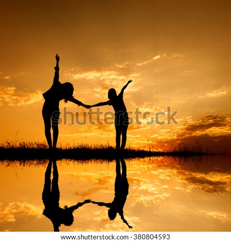 Reflection of Relax of two women standing and sunset silhouette,water reflect with copy space.