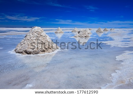 Reflection of salt piles of Salar de Uyuni, giant salt flat in Bolovia, South America - stock photo