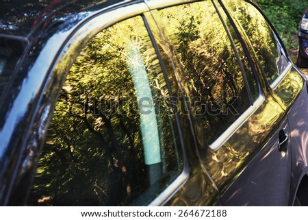 Reflection of seasonal trees in the car window. - stock photo