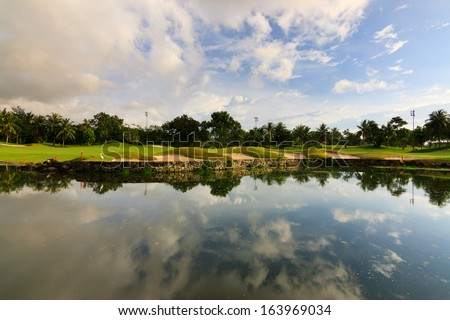 Reflection of sky at a golf course lake - stock photo