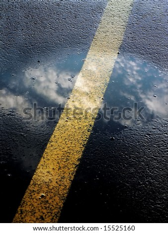 Reflection of sky in puddle on asphalt road - stock photo