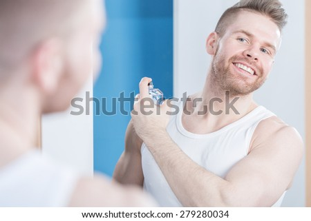 Reflection of smiling handsome guy applying perfume - stock photo