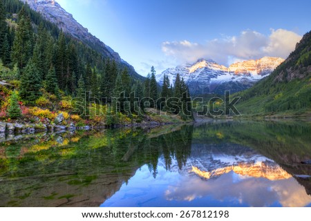 Reflection of Snow capped Maroon Bells in fall, at sunrise. - stock photo