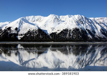 Reflection of snow capped mountains in the water in Alaska