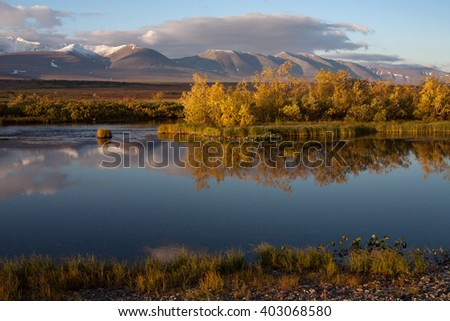 Reflection of snow-covered mountains in a tranquil river. Polar Urals. Russia.