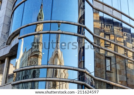 reflection of stone facade on modern glass facade