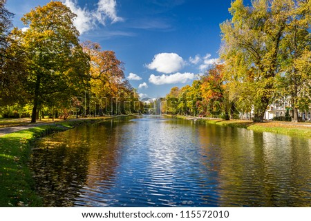 Reflection of the autumn park on the river - stock photo