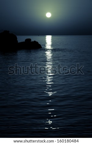 reflection of the moon on the sea surface. moonlit path - stock photo