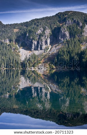 Reflection of the mountain and rock bluff in the still lake below - stock photo