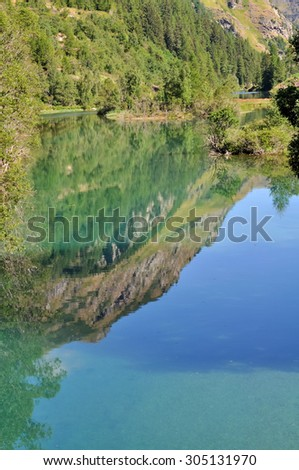 reflection of the mountain on the surface of the lake water - stock photo