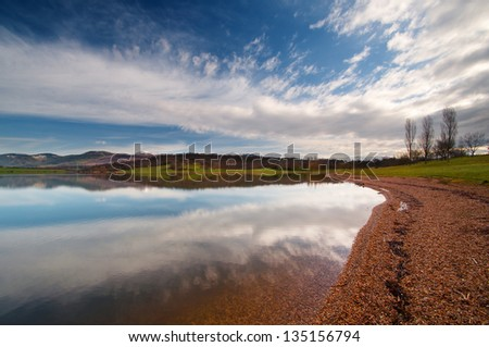 reflection of the mountains and fields in the Garaio reservoir water