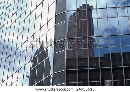 Reflection of the new and old buildings captured together as a reflection in a glass wall - stock photo