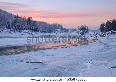 Reflection of the sunset sky in a frozen river. Katun River, Mountain Altai, Siberia, Russia