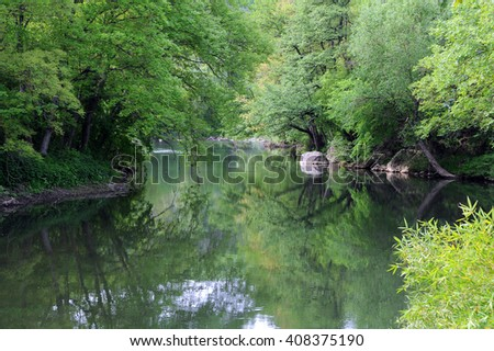 Reflection of the trees in the Yantra river in Bulgaria - stock photo