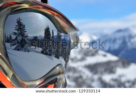 Reflection of the winter mountain landscape in a ski mask. Shallow depth of field. - stock photo