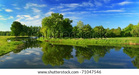 Reflection of trees in the river at dawn - stock photo