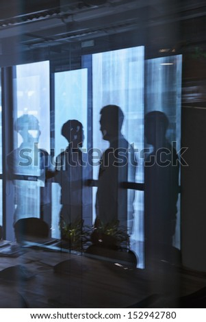 Reflection of two businessmen talking in the office - stock photo