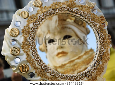 Reflection of Venetian mask in mirror. Selective focus on the mirror frame (left side). - stock photo