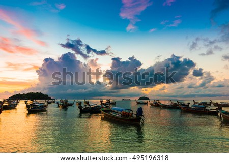 Reflection of Wooden Boat with Burning Sky During Sunrise in Andaman sea