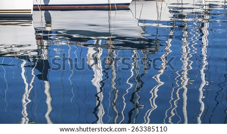 Reflection of yacht masts in the water of the Harbor. Luxury Lifestyle. - stock photo