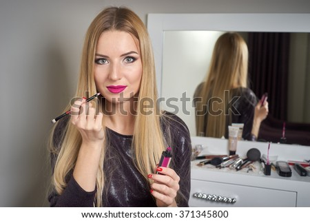 Reflection of young beautiful woman applying her make-up, looking in a mirror - stock photo