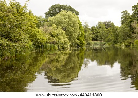 Reflections.  A still and peaceful lake creates a mirror surface for lovely reflections of the summer foliage of the garden around it. An overcast day creates a sombre atmosphere. - stock photo