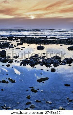 reflections at rocky beach near ballybunion on the wild atlantic way ireland with a beautiful yellow sunset - stock photo